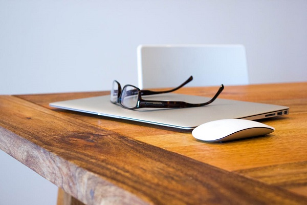 laptop and glasses on wooden table