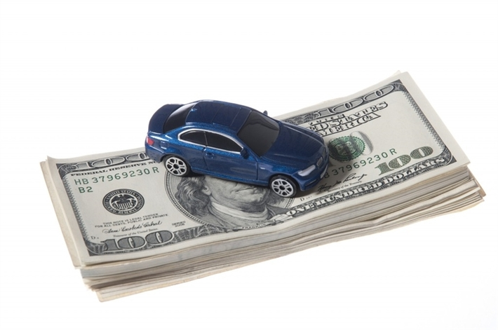 Small blue toy car on a stack of cash.
